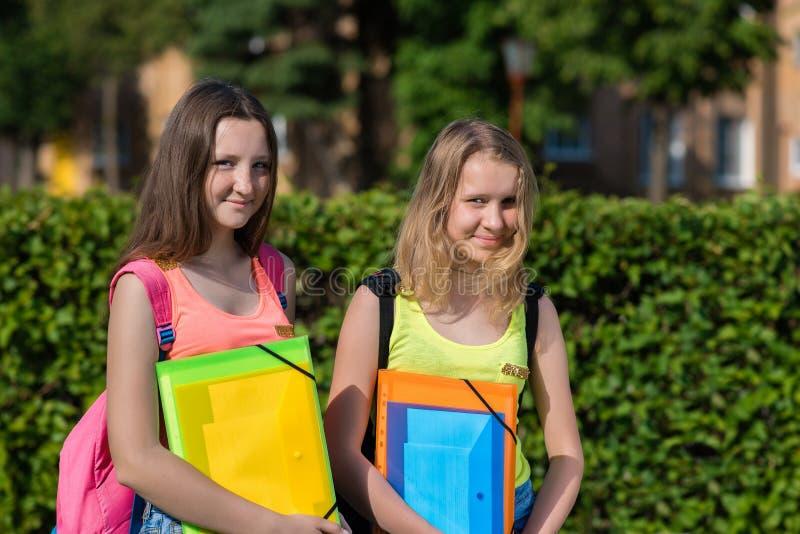De tiener van het twee meisjesschoolmeisje in de zomer in park na school Handen die een omslag van notitieboekjes achter rugzakke stock foto's