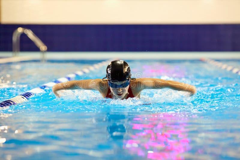 De tiener van het zwemmersmeisje in de pool zwemt binnen vlinder royalty-vrije stock foto's
