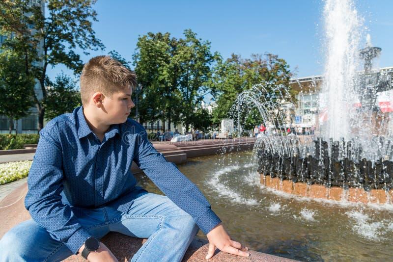 De tiener van 14 jaar zit dichtbij fontein royalty-vrije stock afbeelding