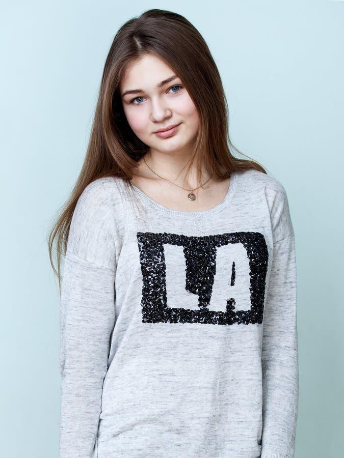 De tiener van Nice in grijze overhemd en jeans stock afbeeldingen