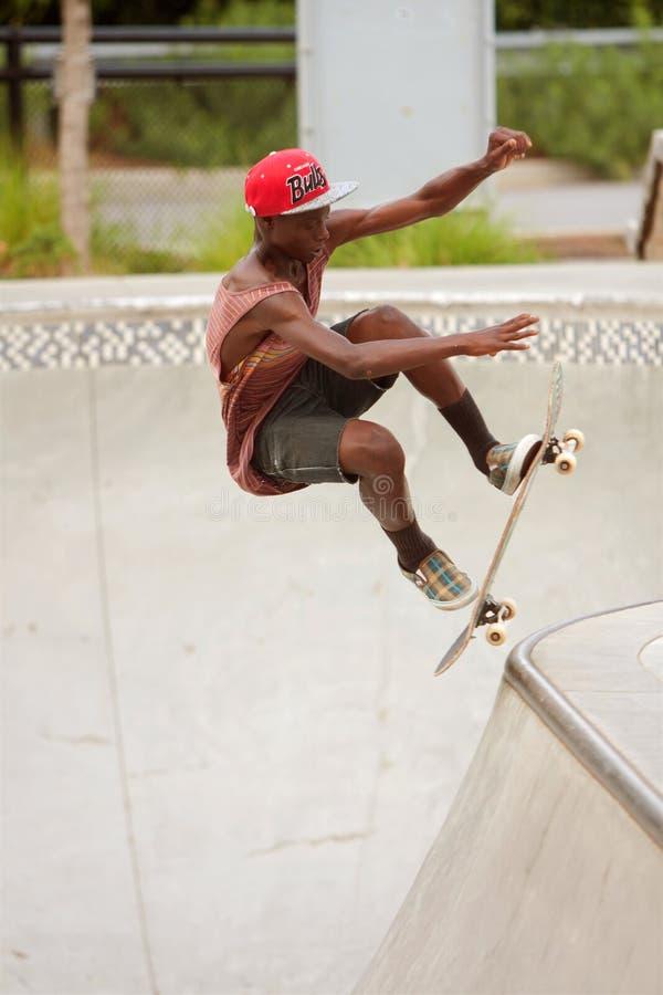 De tiener voert Sprong uit terwijl het Uitoefenen van het Met een skateboard rijden in Skatebo stock foto's