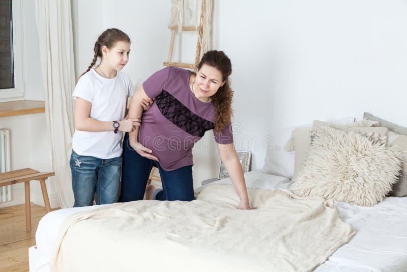 De tienerdochter volgt met zwangere moeder aan bed tijdens pijn in buik van vrouw, slaapkamerbinnenland royalty-vrije stock afbeelding