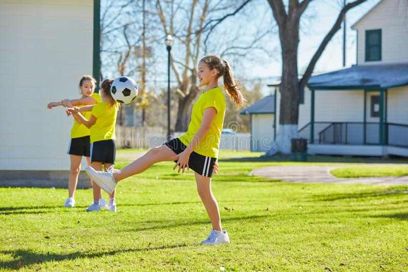 De tienerjaren die van vriendenmeisjes voetbalvoetbal in een park spelen royalty-vrije stock afbeelding