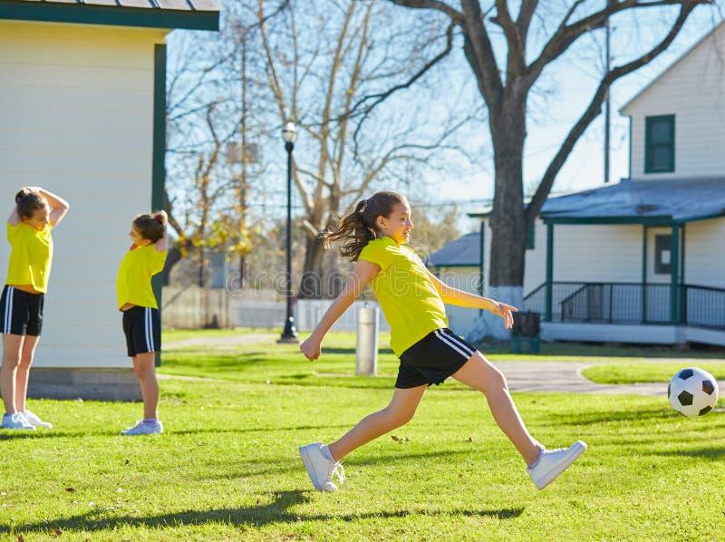 De tienerjaren die van vriendenmeisjes voetbalvoetbal in een park spelen stock foto's