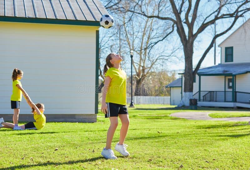 De tienerjaren die van vriendenmeisjes voetbalvoetbal in een park spelen stock fotografie