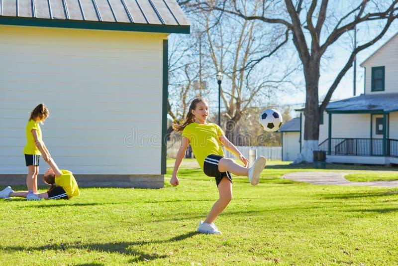 De tienerjaren die van vriendenmeisjes voetbalvoetbal in een park spelen royalty-vrije stock foto