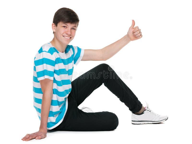 De tienerjongen houdt zijn duim tegen royalty-vrije stock afbeeldingen