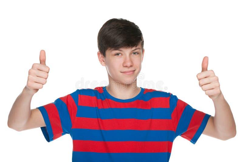 De tienerjongen houdt zijn duimen tegen stock afbeelding