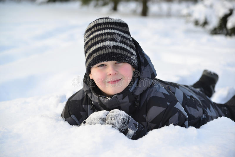 De tienerjongen ligt op sneeuw in het de winterbos royalty-vrije stock afbeelding