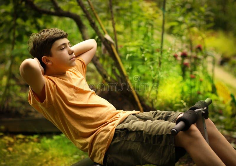 De tienerjongen verhoogt pilates buikoefeningen op draagbare trainer royalty-vrije stock foto's
