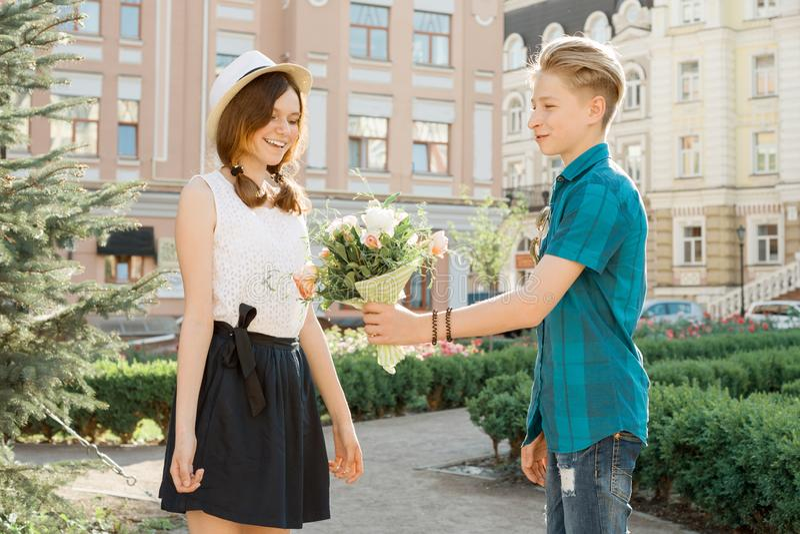 De tienerjongen wenst meisje met boeket van bloemen geluk, de openlucht gelukkige jeugd van het portretpaar stock foto's