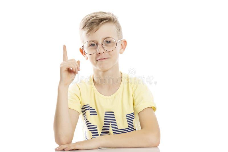 De tienerkerel in glazen hief zijn wijsvinger op omhoog, heeft een idee Zit door de lijst Over witte achtergrond stock foto's