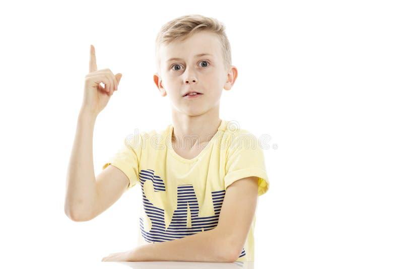De tienerkerel hief zijn wijsvinger op omhoog, heeft een idee Zit door de lijst Over witte achtergrond stock foto