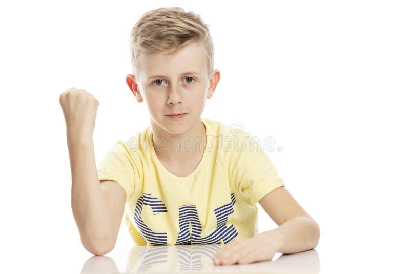 De tienerkerel toont een vuist terwijl het zitten bij de lijst Ge?soleerd over witte achtergrond stock afbeelding