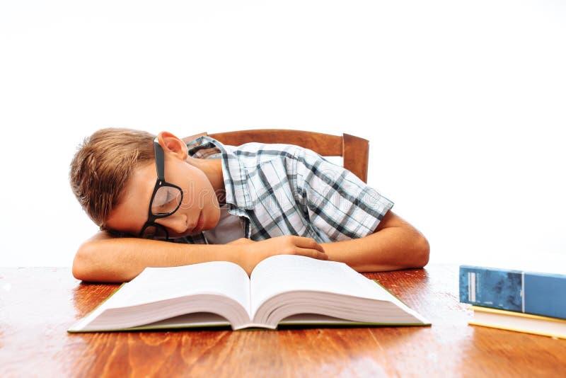 De tienerkerel viel in slaap zitting met boeken, studentenslaap bij Bureau in Studio op witte achtergrond royalty-vrije stock afbeeldingen