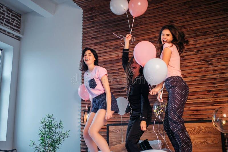 De tieners hebben pret in ruimte Zij dansen en springen op bed De jonge vrouwen houden ballons en het glimlachen De meisjes zijn  royalty-vrije stock foto's