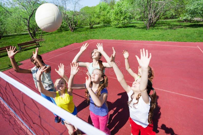 De tieners met wapens spelen omhoog volleyball stock foto's