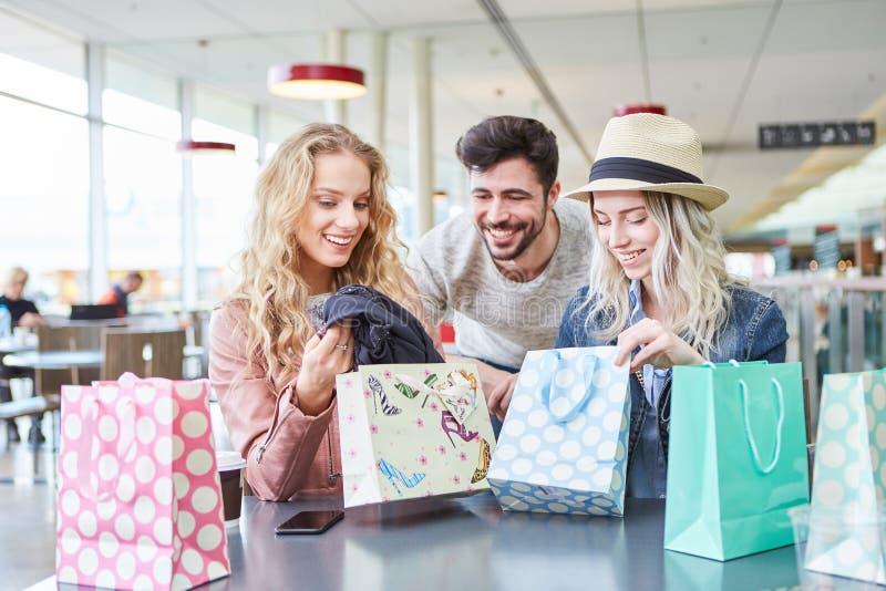 De tieners pakken samen het winkelen zakken uit stock foto