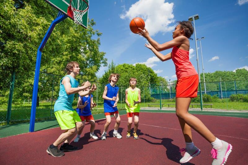 De tieners spelen basketbalspel op grond stock foto's