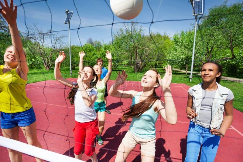 De tieners in team spelen volleyball op het hof royalty-vrije stock foto