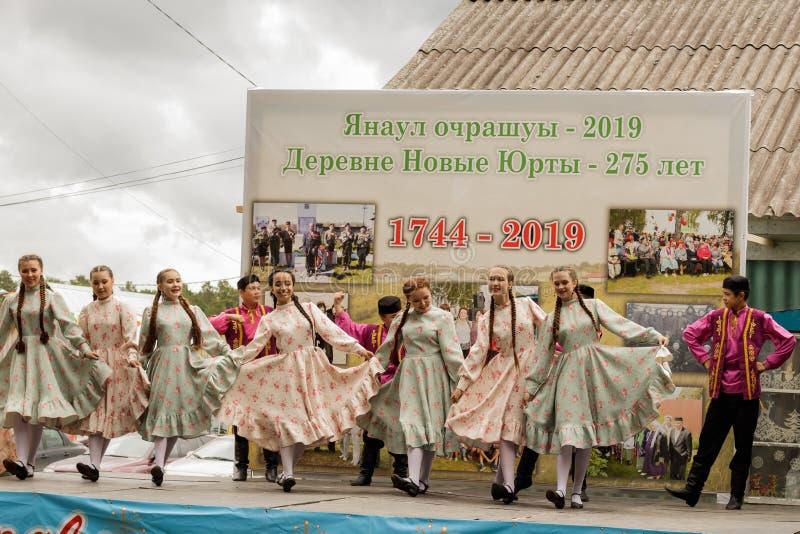 De tieners in traditionele Tatar kleren dansen op stadium tegen de achtergrond van een tribune met historische foto's Feest van stock afbeeldingen