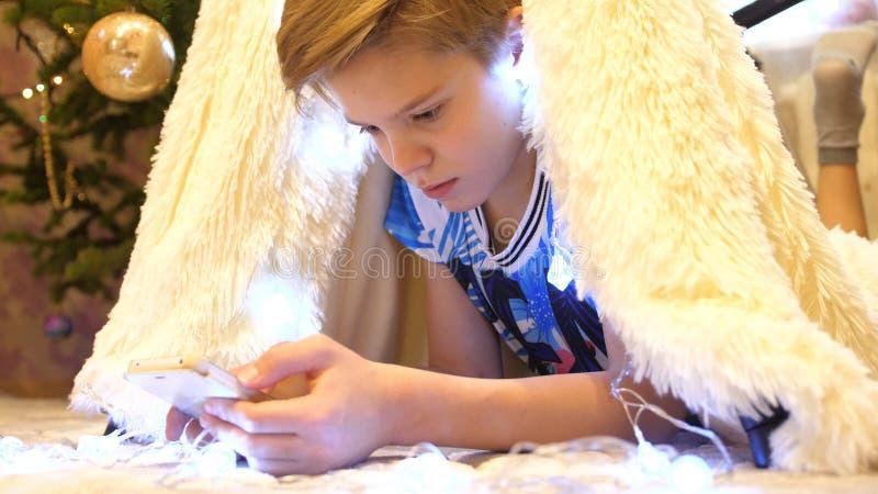 De tienerspelen op smartphone in de ruimte van de kinderen in een tent met een Kerstmislicht Gelukkige kinderjaren stock afbeeldingen