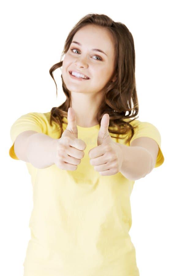 De tienervrouw in vrijetijdskleding het gesturing beduimelt omhoog. royalty-vrije stock afbeeldingen