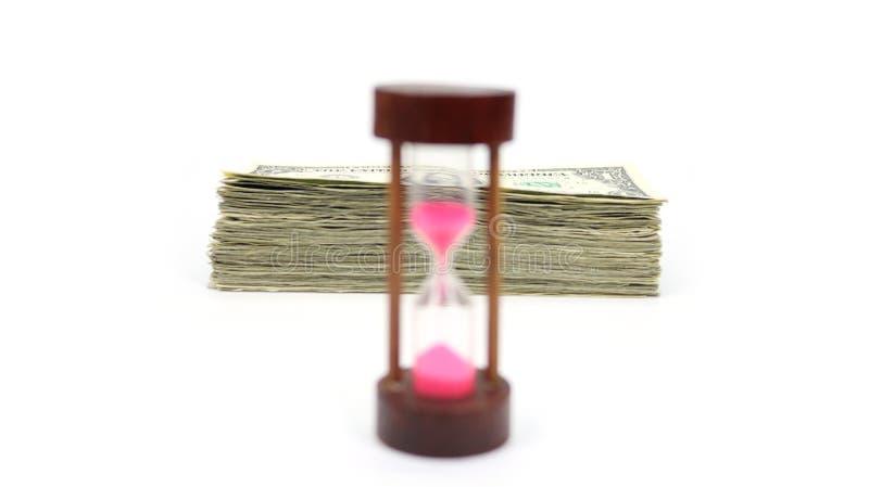 De tijd is Geld met Stapel van Contant geld in Nadruk achter een Houten Zandtijdopnemer op Front And Blurred royalty-vrije stock foto