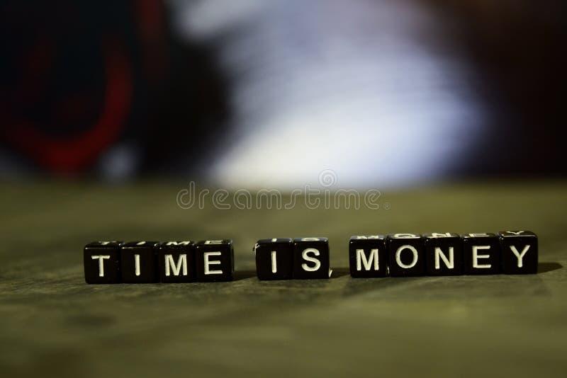De tijd is geld op houten blokken Bedrijfs en financiënconcept stock foto
