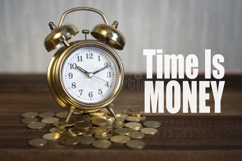 De tijd is geldconcept - de gouden klok van de alarmklok stock foto