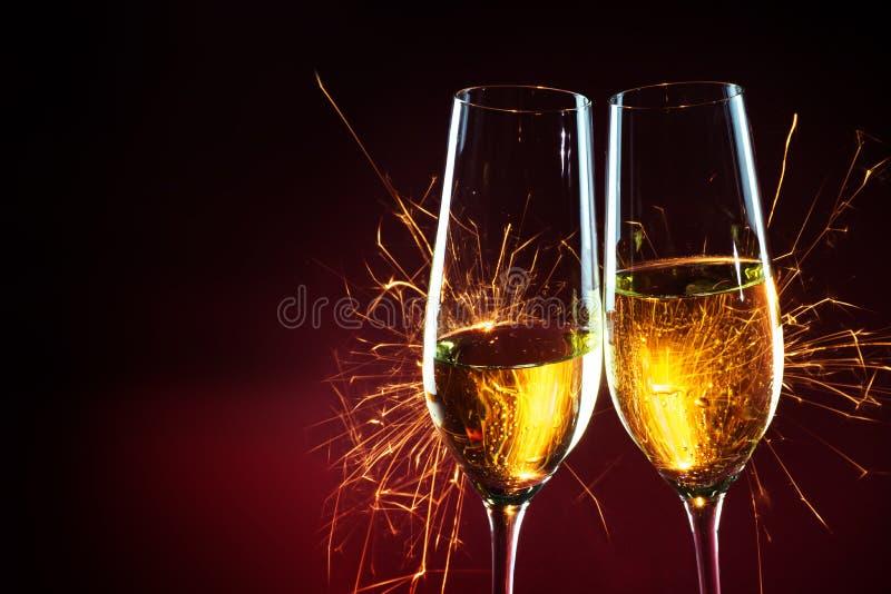 De tijd van de nieuwjaarpartij met twee van champagneglazen en sterretjes aga stock fotografie