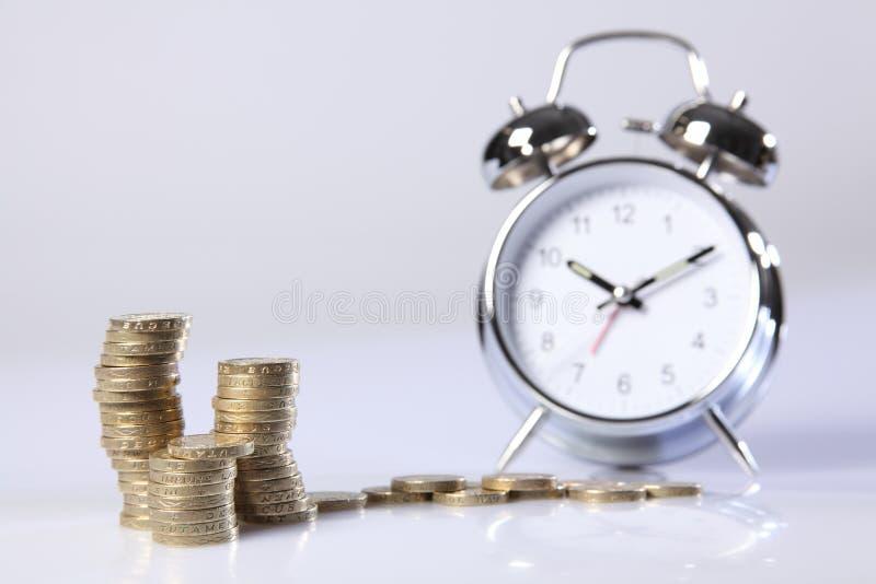 De tijd is van het geld zilveren wekker en pond muntstukken royalty-vrije stock afbeelding
