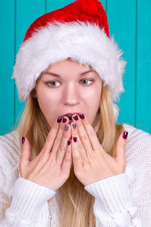 De tijd van Kerstmis Jonge vrouw die de hoeden rode kleding van de Kerstman op blauwe achtergrond dragen stock foto's