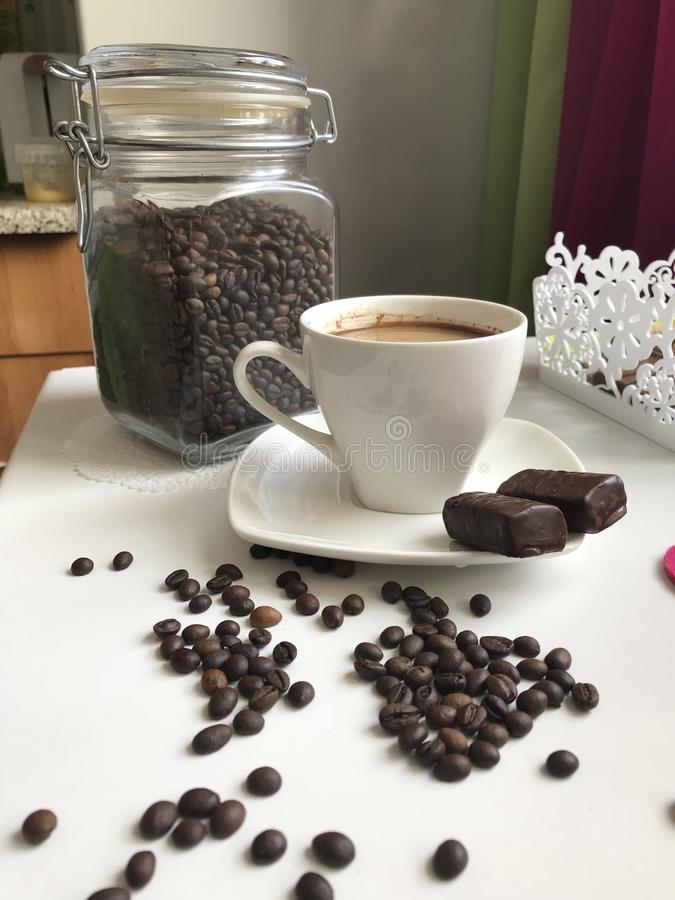 De tijd van de koffie Op de lijst is een kop van gebrouwen aromatische zwarte koffie Naast de schotel zijn chocoladesnoepjes royalty-vrije stock fotografie