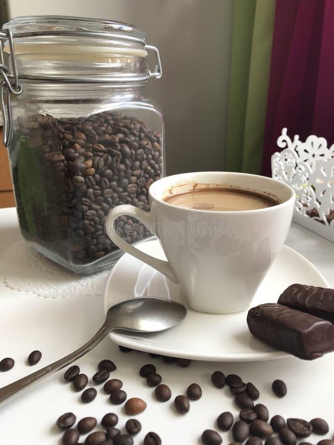 De tijd van de koffie Op de lijst is een kop van gebrouwen aromatische zwarte koffie Naast de schotel zijn chocoladesnoepjes stock afbeeldingen