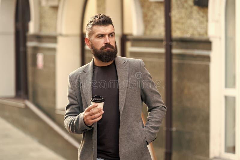 De tijd van de koffie Zakenman in hipsterstijl die meeneemkoffie houden Hipster met beschikbare document kop die in stad lopen stock foto's
