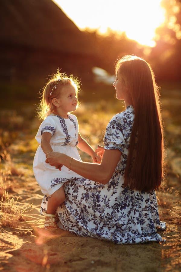De tijd van de moederdochter Portret van moeder en dochter bij aard zitting en het bekijken jeuk andere De dagconcept van de moed stock fotografie