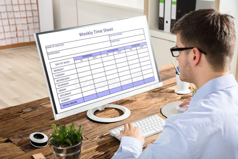 De Tijdblad van zakenmanlooking at weekly op Computer stock afbeeldingen