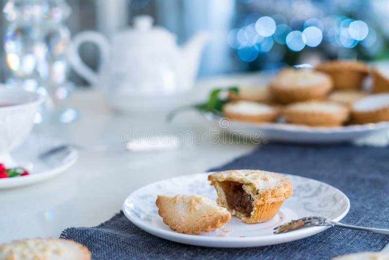 De tijdlijst van het team die met gebroken Mince Pie met het vullen van witte plaat plaatst Traditioneel engels festief gebak met royalty-vrije stock foto