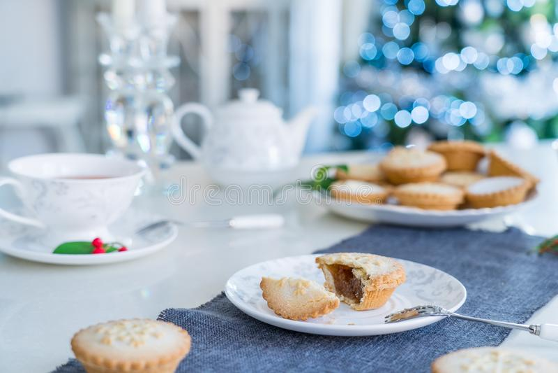 De tijdlijst van het team die met gebroken Mince Pie met het vullen van witte plaat plaatst Traditioneel engels festief gebak met stock afbeeldingen
