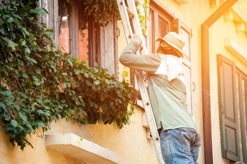 De timmerman beklimt aan eerste verdieping door een ladder aan reparatiehuis royalty-vrije stock fotografie