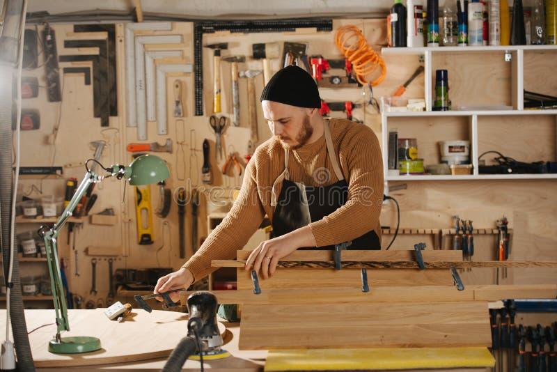De timmerman maakt in bestelling meubilair in een workshop stock foto