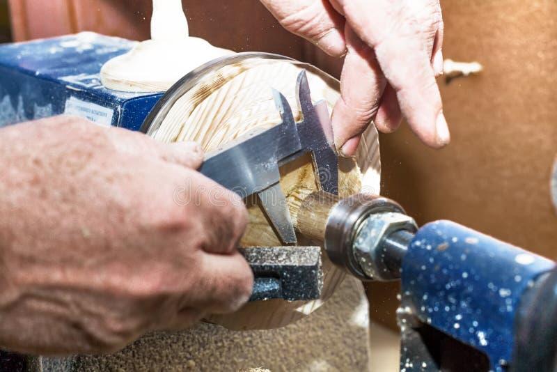 De timmerman maakt het werkstuk op een draaibank De mannelijke handen met een beugel meten de diameter van een houten product stock fotografie