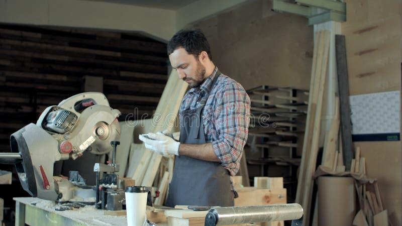 De timmerman met baard maakt iets op zijn slimme telefoon in workshop royalty-vrije stock afbeelding