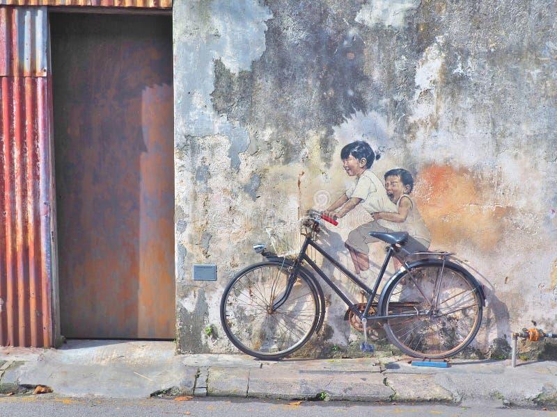 De titel` Jonge geitjes van de straatmuurschildering op een Fiets ` royalty-vrije stock fotografie