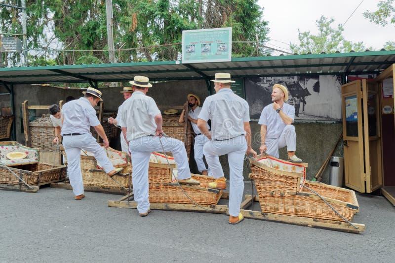 De toboggan bestuurders die met hun mandauto's op toeristen op beginpunt wachten voor toboggan looppas royalty-vrije stock foto
