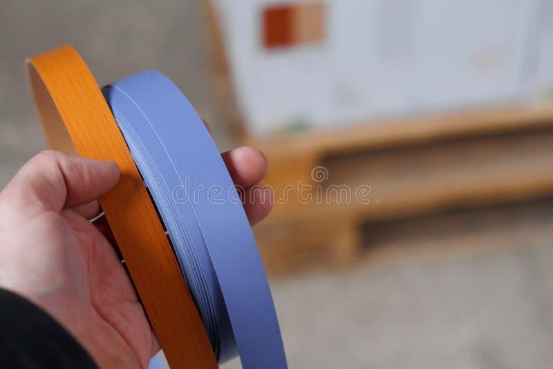 De toebehoren van het meubilair Close-up van een man hand die Multicolored spoelen van de rand en de melanine van pvc voor de ver stock foto