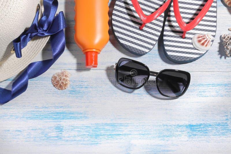 De toebehoren van het strand de zomerhoed met vlokken, room, glazen en overzeese shells op een blauwe houten achtergrond Hoogste  royalty-vrije stock foto's