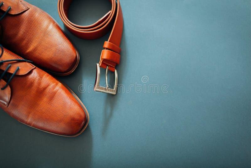 De toebehoren van de zakenman Bruine leerschoenen, riem, parfum, gouden ringen Mannelijke manier Zakenman stock foto's