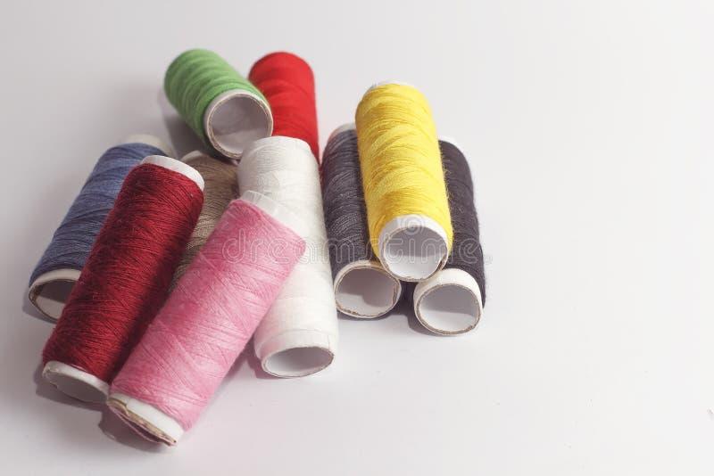 De toebehoren voor het naaien liggen op een witte achtergrond Multicolored rollen van draden stock foto's